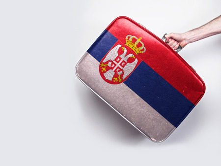 Serbia flag on a vintage leather suitcase.
