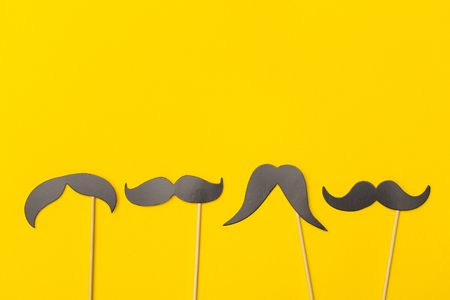 Moustache on a stick on a bright yellow background