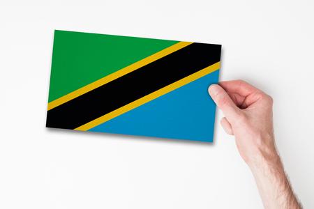 Male hand holding tanzania flag