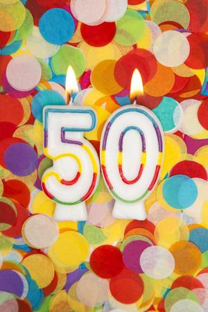 Celebration candle number 50 on a confetti background Foto de archivo