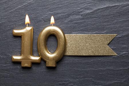 Gouden nummer 10 vieringskaars met glitteretiket Stockfoto