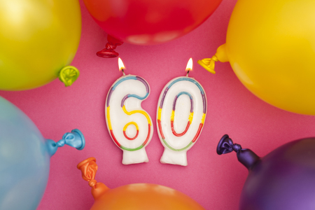 Happy Birthday number 60 celebration candle with colorful balloons