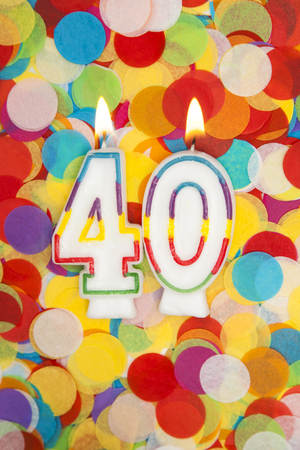 Celebration candle number 40 on a confetti background