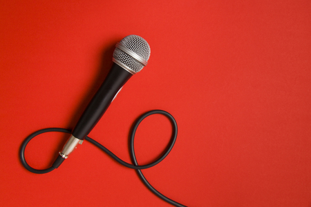 microphone and lead on a bright red background.