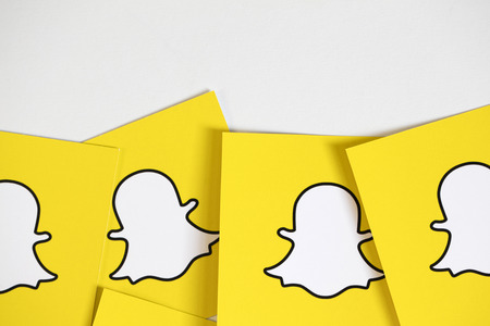 OXFORD, UK - DECEMBER 5th 2016: Snapchat logos printed onto paper. Snapchat is a popular social media application for sharing messages, images and videos Editorial