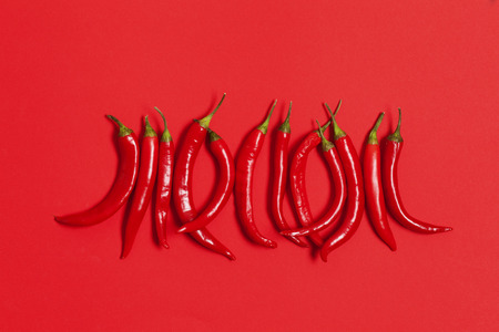 Red chili peppers arranged on a bright red background