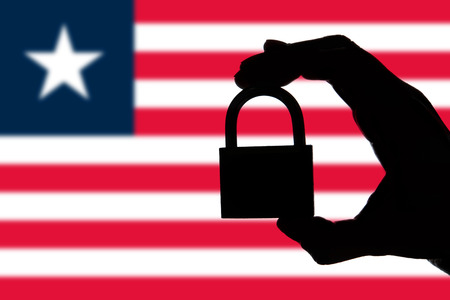 Liberia security. Silhouette of hand holding a padlock over national flag