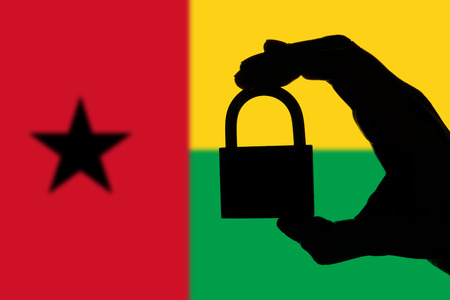 Guinea Bissau security. Silhouette of hand holding a padlock over national flag