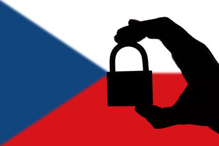Czech Republic security. Silhouette of hand holding a padlock over national flag
