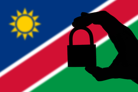 Namibia security. Silhouette of hand holding a padlock over national flag