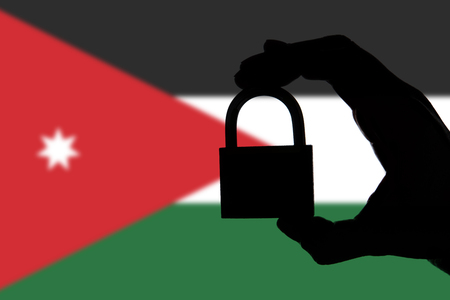 Jordan security. Silhouette of hand holding a padlock over national flag