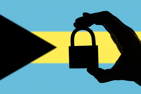 Bahamas security. Silhouette of hand holding a padlock over national flag Stock Photo
