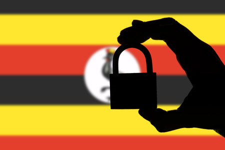 Uganda security. Silhouette of hand holding a padlock over national flag