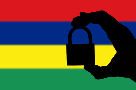 Mauritius security. Silhouette of hand holding a padlock over national flag