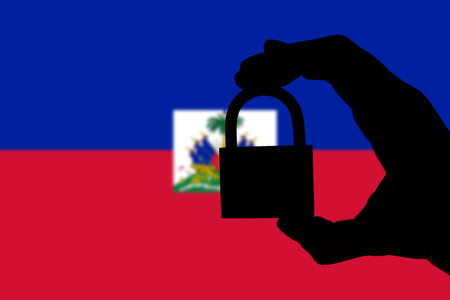 Haiti security. Silhouette of hand holding a padlock over national flag