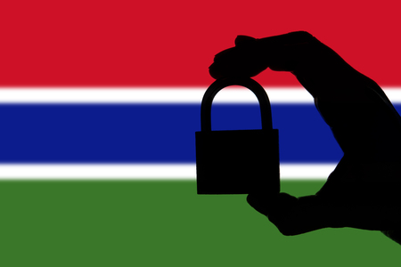 Gambia security. Silhouette of hand holding a padlock over national flag