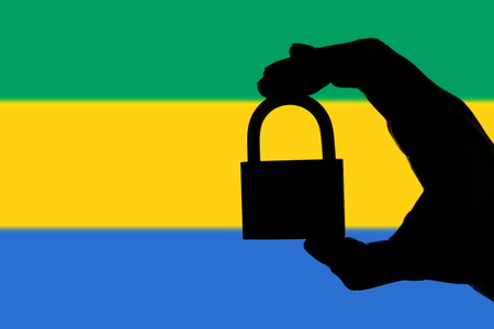 Gabon security. Silhouette of hand holding a padlock over national flag Stock Photo