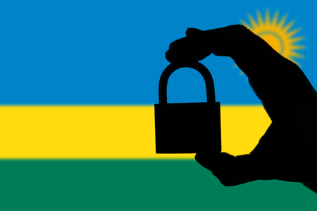 Rwanda security. Silhouette of hand holding a padlock over national flag Stock Photo