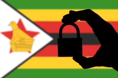 Zimbabwe security. Silhouette of hand holding a padlock over national flag Stock Photo