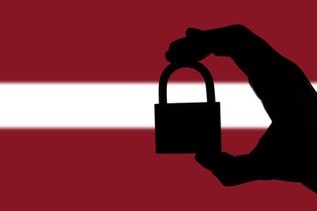 Latvia security. Silhouette of hand holding a padlock over national flag