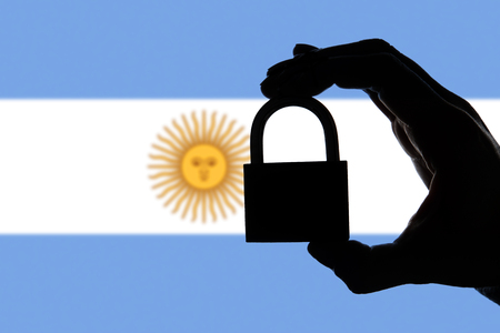 Argentina security. Silhouette of hand holding a padlock over national flag