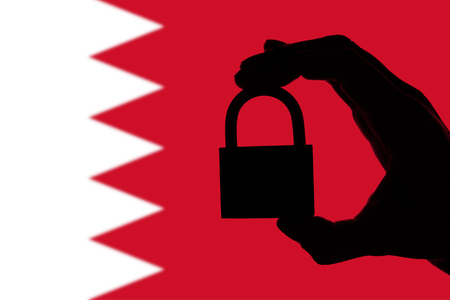 Bahrain security. Silhouette of hand holding a padlock over national flag