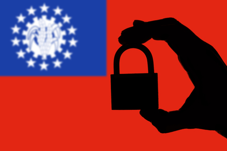Myanmar security. Silhouette of hand holding a padlock over national flag Stock Photo