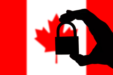 Canada security. Silhouette of hand holding a padlock over national flag Stock Photo