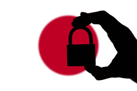 Japan security. Silhouette of hand holding a padlock over national flag