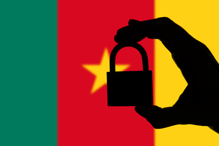 Cameroon security. Silhouette of hand holding a padlock over national flag Stock Photo