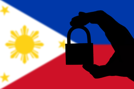 Philippines security. Silhouette of hand holding a padlock over national flag Stock Photo
