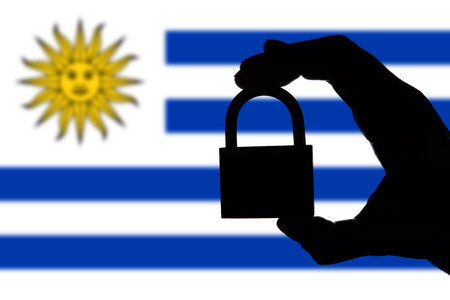 Uruguay security. Silhouette of hand holding a padlock over national flag
