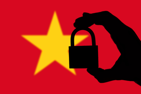 Vietnam security. Silhouette of hand holding a padlock over national flag Stock Photo