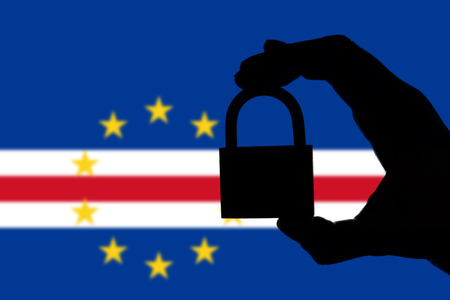Cape Verde security. Silhouette of hand holding a padlock over national flag Stock Photo