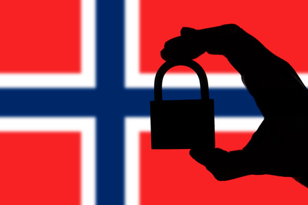 Norway security. Silhouette of hand holding a padlock over national flag