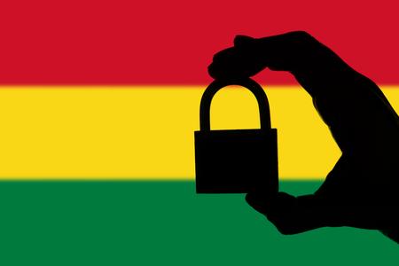 Seguridad de Bolivia Silueta de mano sosteniendo un candado sobre bandera nacional Foto de archivo
