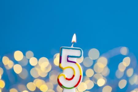 Feiernde Kerze der Nr. 5 gegen helle Lichter und blauen Hintergrund Standard-Bild