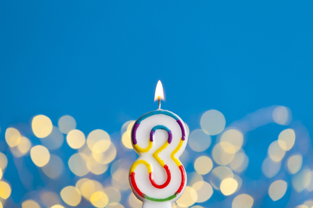 Number 3 birthday celebration candle against a bright lights and blue background Stock Photo