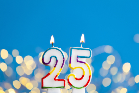 Number 25 birthday celebration candle against a bright lights and blue background