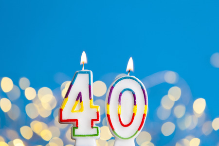 Number 40 birthday celebration candle against a bright lights and blue background