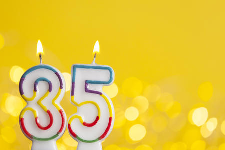 Number 35 birthday celebration candle against a bright lights and yellow background