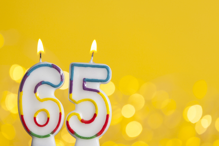 Number 65 birthday celebration candle against a bright lights and yellow background