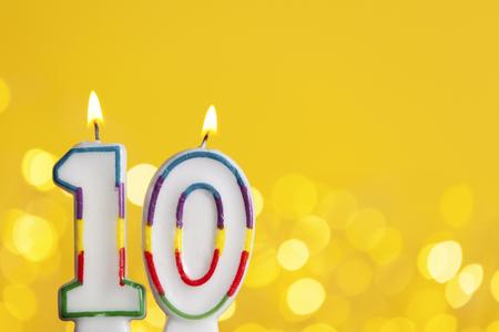 Feiernde Kerze der Nr. 10 gegen helle Lichter und gelben Hintergrund