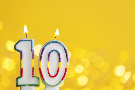 Number 10 birthday celebration candle against a bright lights and yellow background
