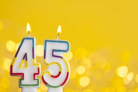 Number 45 birthday celebration candle against a bright lights and yellow background