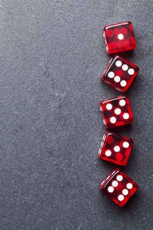 A set of red dice on a slate background. Betting and gambling concept