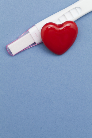 Pregnancy test with a red heart on a blue background