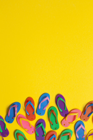 collection of colourful summer flip flop sandals on a bright yellow background Banque d'images