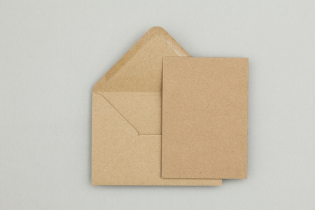 Blank brown kraft paper card and envelope on a grey background Foto de archivo
