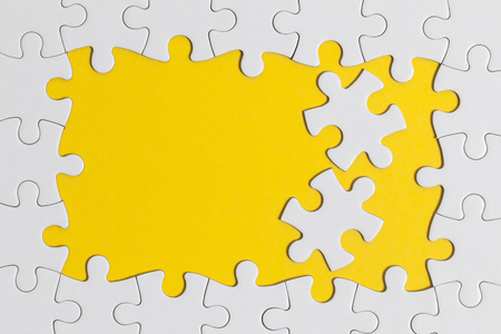 White jigsaw puzzle pieces on a yellow background. Business solution concept
